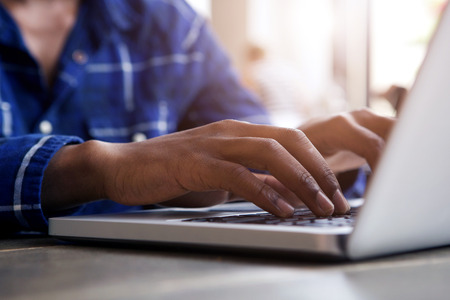 Close up portrait of male hands typing on laptop computer
