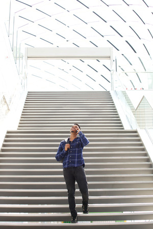 cool guy: Full length portrait of cool young black guy on stairs talking on cell phone Stock Photo
