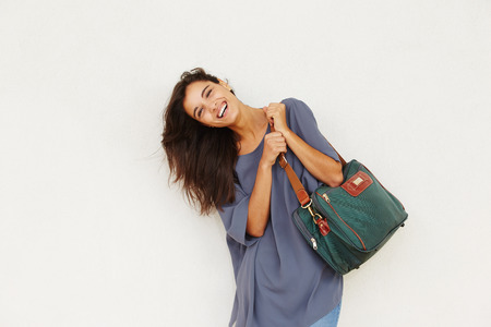 woman bag: Portrait of beautiful young woman smiling with bag against white wall