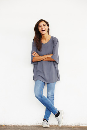 Full body portrait of female fashion model standing against wall with arms crossed and laughing