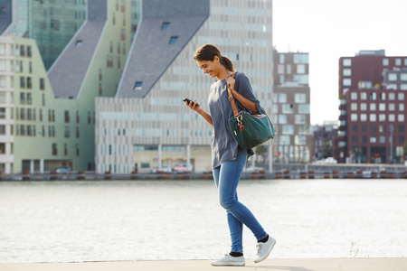 携帯電話が付いている都市に水を歩いて幸せな若い女性の完全な長さの肖像画