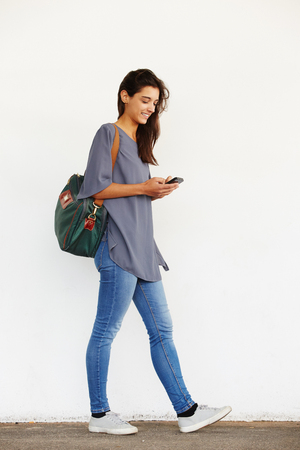 Full length portrait of beautiful young woman walking outside and reading text message on her mobile phone Foto de archivo