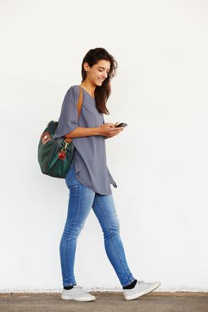 Retrato de corpo inteiro de mulher jovem e bonita andando lá fora e lendo a mensagem de texto em seu telefone móvel Foto de archivo