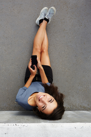 view to outside: Top view portrait of happy woman sitting outside with smartphone and smiling Stock Photo