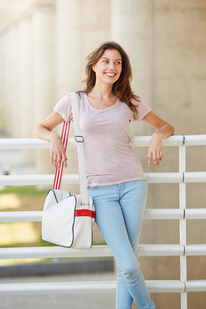 leaning: Portrait of attractive young woman traveler smiling with bag