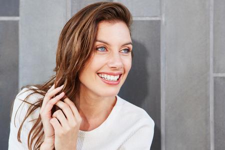 Ciérrese encima del retrato de la mujer joven atractiva con sonrisa hermosa