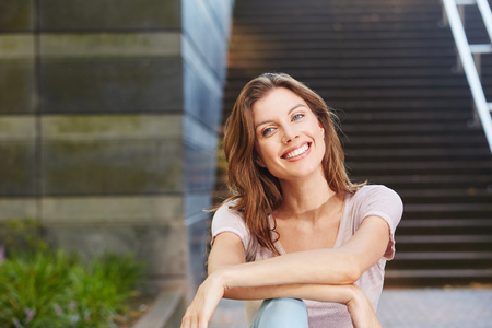 mujer sola: Portrait of cheerful young woman sitting outdoors and smiling Foto de archivo