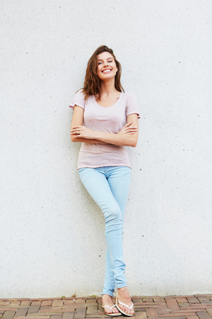 Full body portrait of happy and beautiful young woman leaning against wall