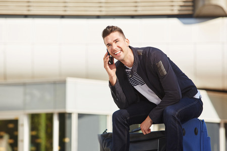 waiting phone call: Portrait of smiling man waiting at station with luggage on phone call