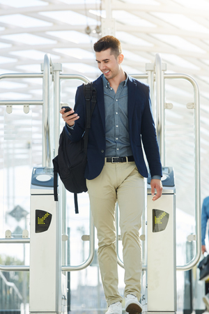 Full length portrait of business man walking through turnstile with mobile phone Stock Photo