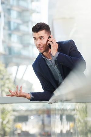 annoyed: Portrait of annoyed business man talking on mobile phone Stock Photo