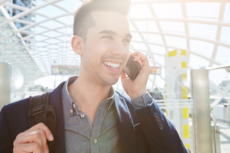 phone business: Close up portrait of smiling traveling business man on mobile phone call with bag