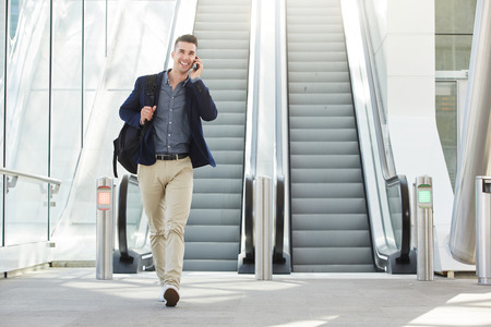business man phone: Full body portrait of fashionable happy man on phone call by escalator