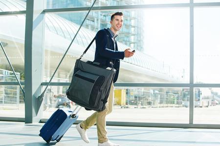 Ganzkörper-Porträt des Menschen mit Gepäck und Telefon in der Station zu Fuß lächelnd