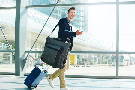 Full body portrait of man walking with luggage and phone in station smiling