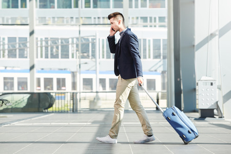 Full length side portrait of business man walking with luggage on telephone call at station