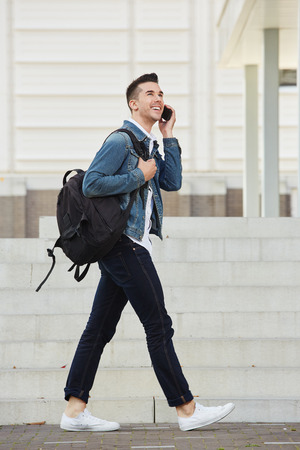 Full length portrait of smiling young man walking outside with bag and cellphone