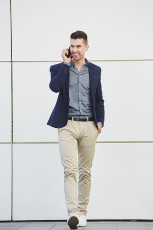 cuerpo hombre: Full length portrait of cheerful young business man talking on mobile phone