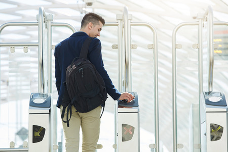 validating: Rear portrait of business man at automated turnstile with cellphone