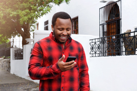 cool guy: Portrait of a cool black guy smiling outside with cell phone