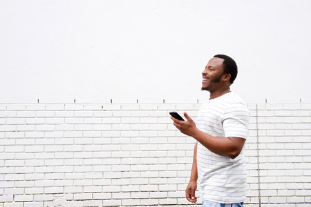 cool guy: Portrait of cool african american guy walking with mobile phone Stock Photo