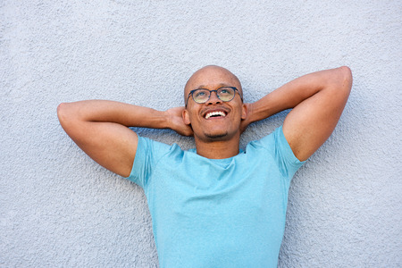 contemplation: Portrait of african american man smiling with glasses looking up in contemplation