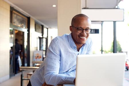 ハンサムなアフリカの実業家のノート パソコンでの作業の肖像画