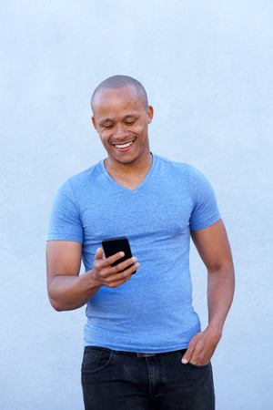 cool guy: Portrait of cool african guy smiling with cellphone Stock Photo