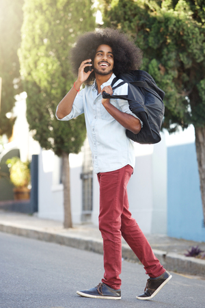 Full length portrait of happy man walking outside with phone and bag Stock Photo