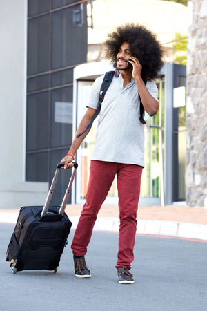 Full length portrait of african man with suitcase talking on cellphone in city