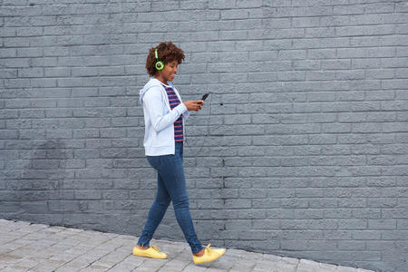 sidewalk: Full body portrait of african woman walking and listening to music on mobile phone