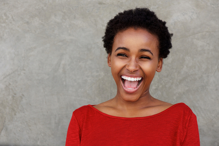 Portrait of beautiful young black woman laughing with open mouth