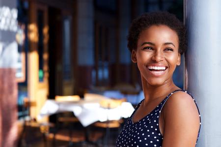 Portrait de côté de la souriante jeune femme noire debout à l'extérieur Banque d'images