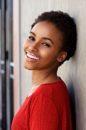 leaning against: Side portrait of smiling young black woman leaning against wall
