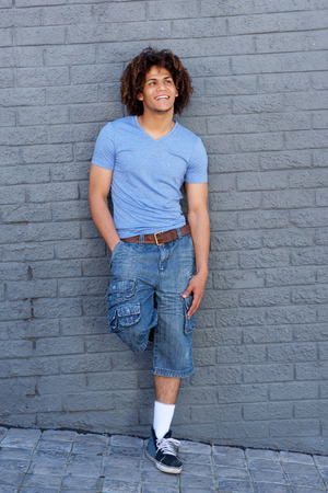 black guy: Full body portrait of cool young guy with curly hair smiling