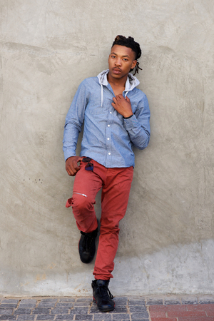 Full length portrait of cool african man with dreadlocks leaning against wall Stock Photo - 70146630