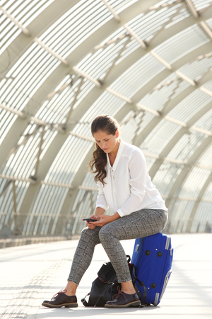 mujer con maleta: Full portrait of beautiful serious woman sitting on suitcase using mobile