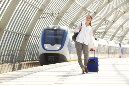 Full portrait of happy woman walking with suitcase at train station