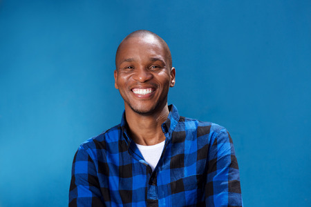 Close up portrait of smiling young african man standing with his arms crossed against blue background Stock Photo