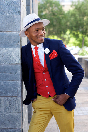 suave: Portrait of stylish young african american man in suit and hat standing outdoors