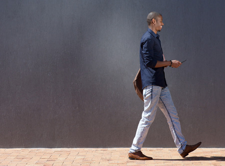 Profile portrait of black male student walking with tablet