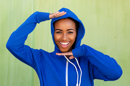 black girl: Portrait of cool young black woman smiling with hands raised