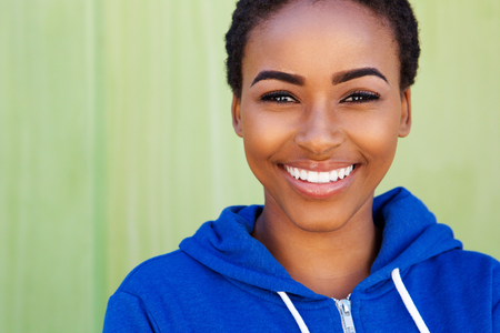 woman smiling: Close up portrait of smiling young black woman against green background Stock Photo