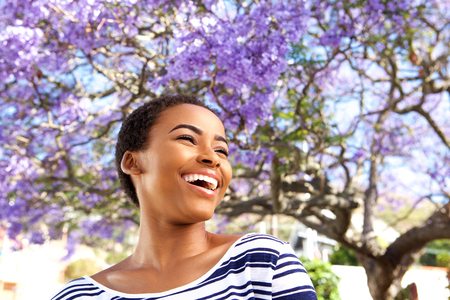 Portrait of attractive young black woman laughing outdoors by flower tree