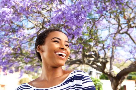 Portret van aantrekkelijke jonge zwarte vrouw buitenshuis lachen door bloem boom Stockfoto - 71517809