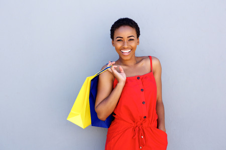 african fashion: Portrait of beautiful young black woman smiling with shopping bags Stock Photo