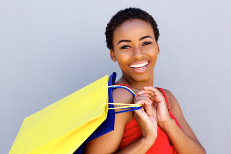 Close up portrait of young woman smiling with shopping bags