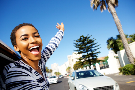 Portrait of young cheerful woman hanging outside car window with arms raised