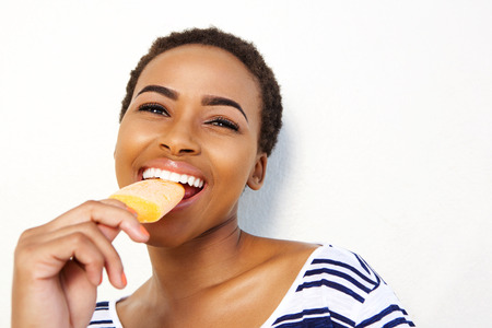 Portrait of young black female eating ice cream against white wall Stock Photo