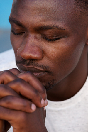 Close up portrait of young african man praying with hands clasped and eyes closed